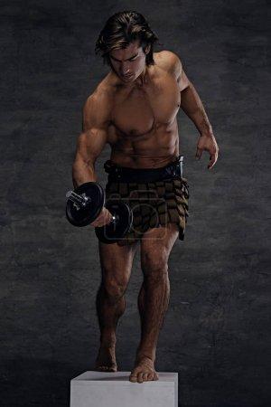 Athletic shirtless male posing on podium