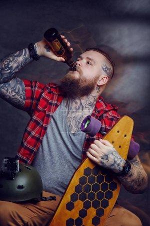 Tattooed skateboarder drinking beer