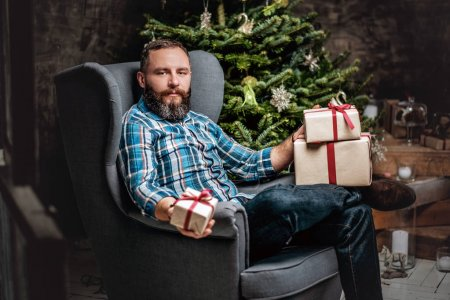Photo for Portrait of bearded middle age man with gift boxes over fir tree in background. - Royalty Free Image