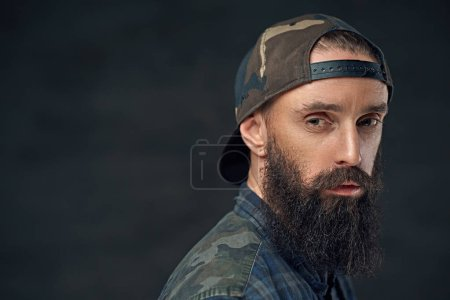 Photo for Close up portrait of bearded man in military cap and plaid flannel shirt over dark grey background. - Royalty Free Image