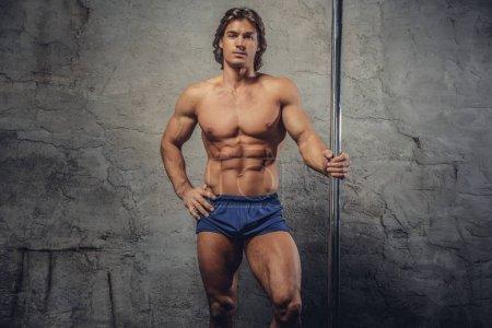 Photo pour Portrait d'un homme athlétique torse nu tient barre d'haltère sur fond gris . - image libre de droit