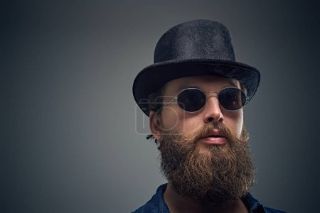 Photo for Close up portrait of bearded man in sunglasses and top hat on grey background. - Royalty Free Image