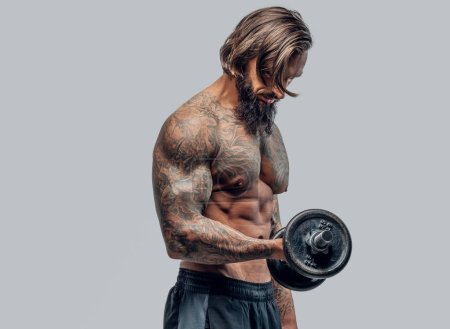 Shirtless bearded man with tattooed body holding dumbbell on light grey background.