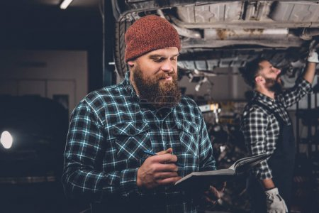 Mechanics inspecting car engine
