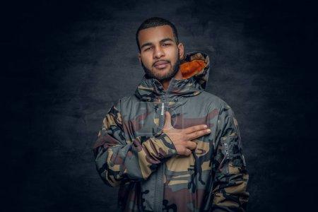 Photo pour Portrait en studio de l'homme noir vêtu d'une veste militaire. - image libre de droit