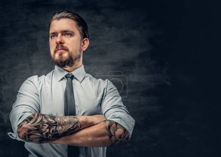Photo for Stylish bearded man with tattooed arms, dressed in a shirt posing over grey background. - Royalty Free Image