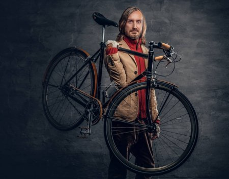 Man holds bicycle on his shoulder