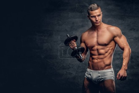 Shirtless muscular man holds dumbbell