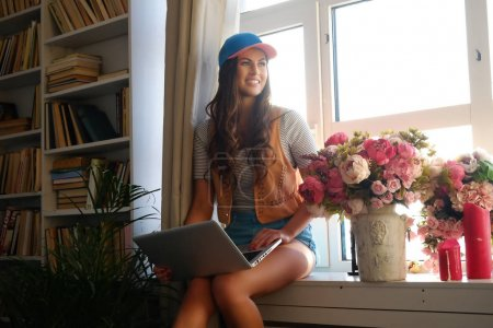 Smiling woman holds laptop