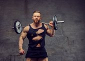 Bearded bodybuilder holds a barbell