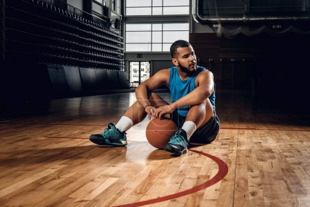 Black basketball player sits on a floor