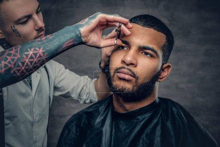 Tattooed barber makes haircut