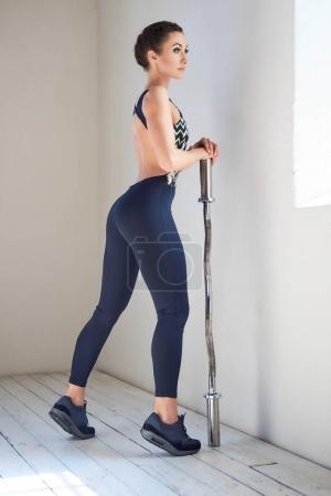 Sporty female holds barbell