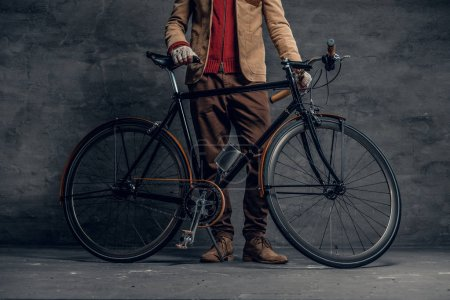 Photo for Man posing with single speed bicycle over grey background. - Royalty Free Image