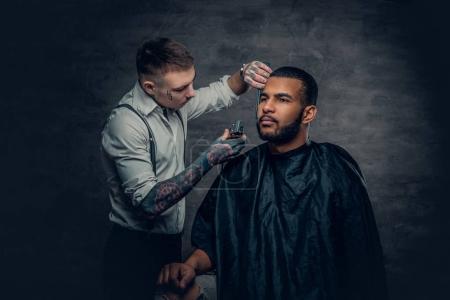 Tattooed barber cutting the beard