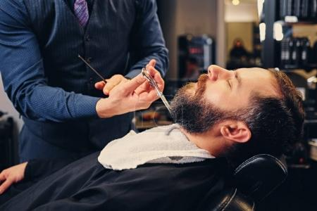 Photo for Close up image of barber cutting beard of a man. - Royalty Free Image