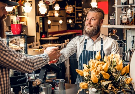 Photo for Positive bearded barista selling coffee to a consumer in a coffee shop. - Royalty Free Image