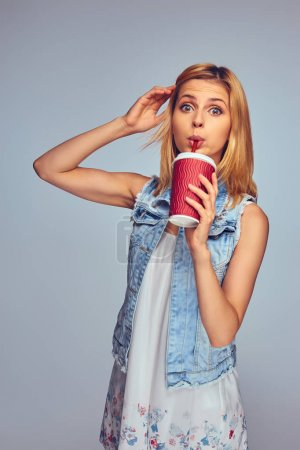 Female holds paper red cup