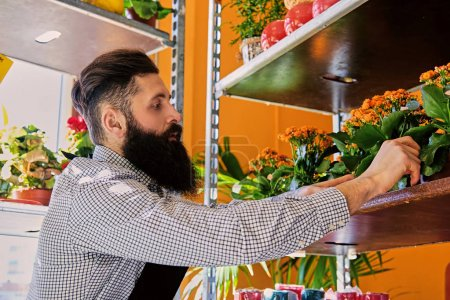 Photo for Bearded tattooed man works in a flower market shop. - Royalty Free Image