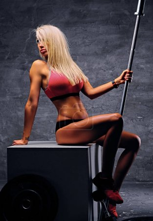 Sporty blonde female holds barbell