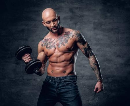 Brutal man with tattoos holds dumbbell