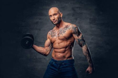 Muscular man holds dumbbell