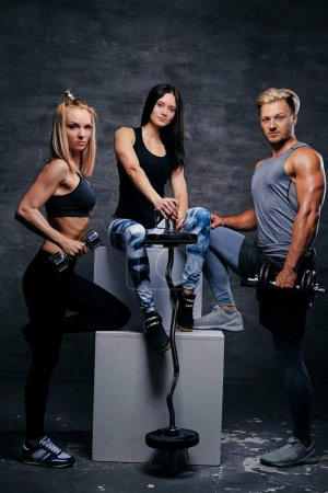 Sporty blond and brunette women and an athletic man over grey ba