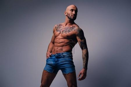Muscular man with tattoos on his torso