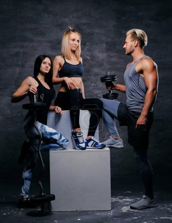 Athletic people posing with dumbbells
