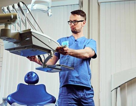 Photo pour Dentiste mâle dans une salle avec des équipements médicaux sur fond. - image libre de droit