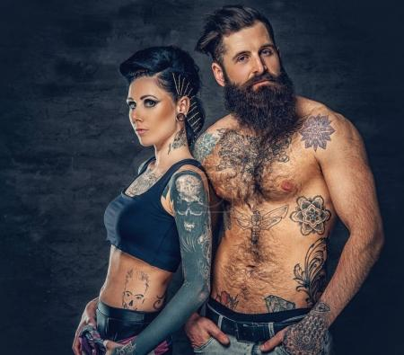 Studio portrait of tattooed couple