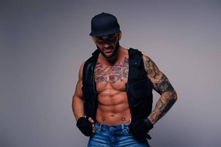 Tattooed man dressed in a jeans