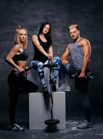 Blond and brunette women and an athletic man posing on a white b