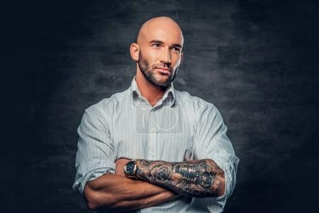 Man in a white shirt with tattooed crossed arms.