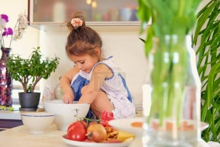Little girl sits trying to cook
