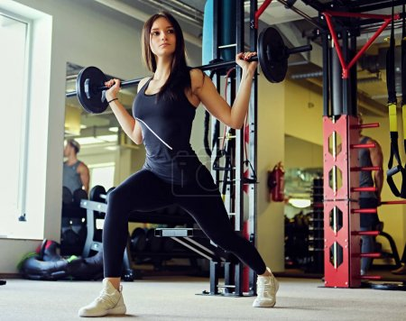 Sporty female doing squats with barbell