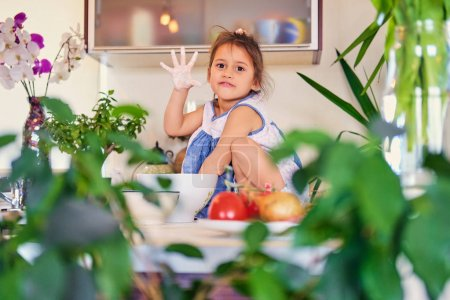 Little girl sits prepares dough