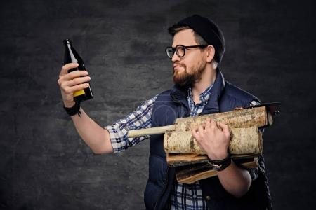 Man holds firewood and bottled beer