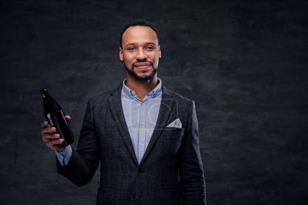 Black man holding beer bottle