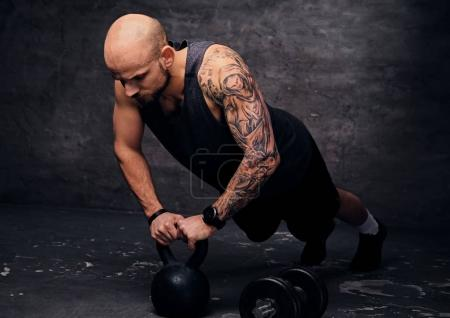 Man doing push ups on Kettlebell.