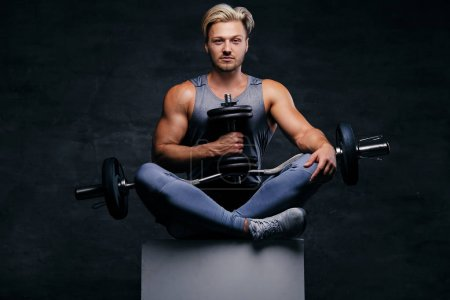 Blond sporty male holds dumbbell set