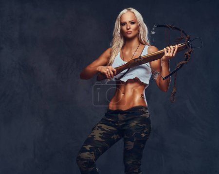 An attractive blond female dressed in a bra and military pants holds an ancient wooden crossbow over grey background.