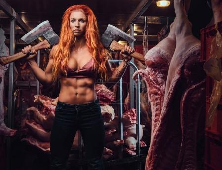 The redhead athletic female holds two axes in a meat factory.