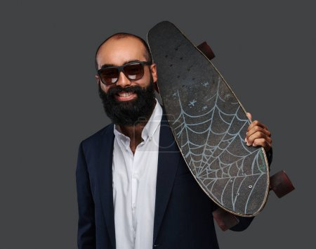 Studio portrait of a bearded male in a business suit with skateboard on the shoulder.