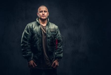 Portrait of a serious brutal male in casual clothes on a dark background.