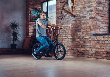 Photo for Handsome man in t-shirt and jeans sitting on a BMX. Studio shot. - Royalty Free Image
