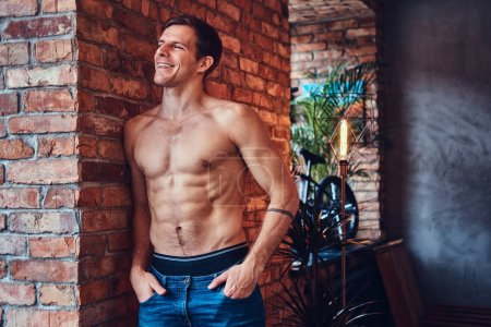 A sexy tattoed shirtless man leans against the brick wall. Smiling and looking away.
