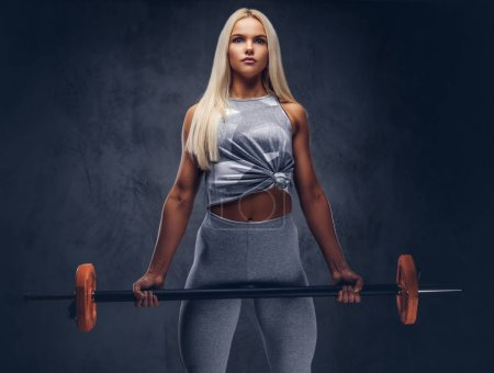 A sporty blonde fitness woman posing with a barbell in a studio over gray background. Front view.