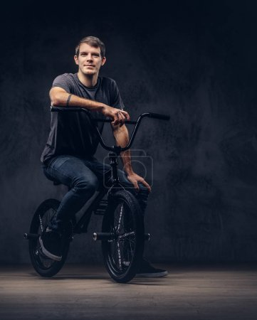 Photo for Handsome man in t-shirt and jeans sitting on a BMX. Isolated on a dark background. - Royalty Free Image
