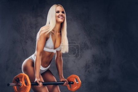 A sporty woman in a white underwear holds an orange barbell in a studio against a gray background.